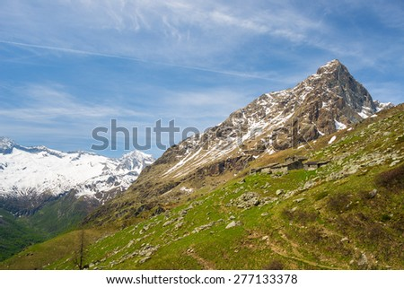 Pasture and shepherd's huts set in amazing alpine scenery in spring season. Majestic snowcapped mountain peak in the background. Piedmont, italian Alps. - stock photo