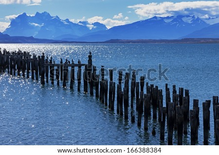 Patagonia bay and mountains from Puerto Natales with cormorants on old pilings and Mount Balmaceda across Last Hope Sound - stock photo