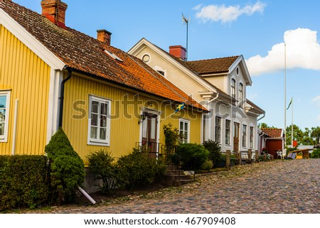 Pataholm, Sweden - August 9, 2016: Part of the rustic old buildings along the village street leading up to the town square. Street is covered with granite stone boulders as pavement.