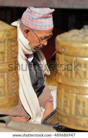 PATAN, NEPAL - DECEMBER 19, 2014: A Nepalese man reading Buddhist prayers at the Golden Temple with prayer wheels in the foreground