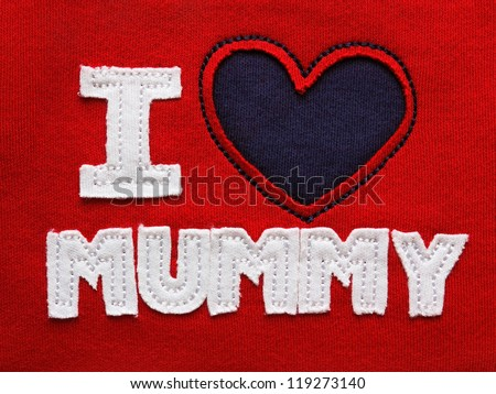 Patchwork 'I love mummy' on the red fabric - stock photo