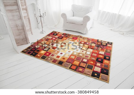 Patchwork quilt. Part of patchwork quilt as background. White interior. White armchair. Klimt print. - stock photo