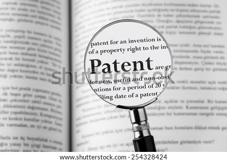 Patent holding Magnifying Glass . Studio Shot . - stock photo