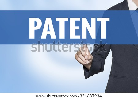 Patent word on virtual screen touch by business woman blue background - stock photo