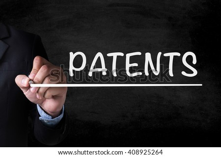 PATENTS and Businessman drawing  Page on blackboard - stock photo