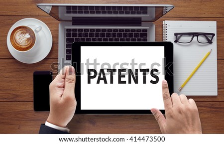 PATENTS, on the tablet pc screen held by businessman hands - online, top view - stock photo
