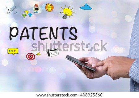 PATENTS person holding a smartphone on blurred cityscape background - stock photo