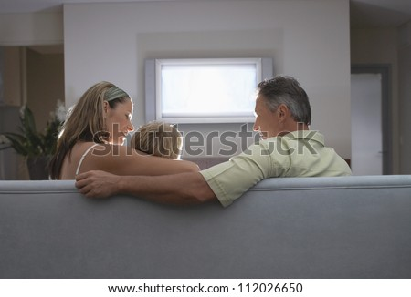 Patents with son on sofa watching TV at home - stock photo