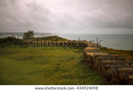 Path at the Top of the Cliffs at Fecamp Normandy with wooden fence and barbed wire - stock photo