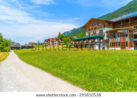 Path in alpine village with traditional countryside houses on shore of Weissensee lake in summer landscape of Alps Mountains, Austria - stock photo