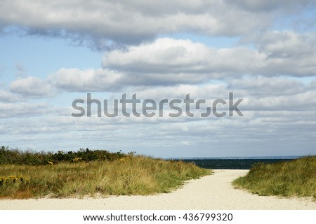 Path in sand leads through marsh grass to Buzzards Bay - stock photo