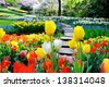 Path in spring park surrounded by multicolor flowers - stock photo