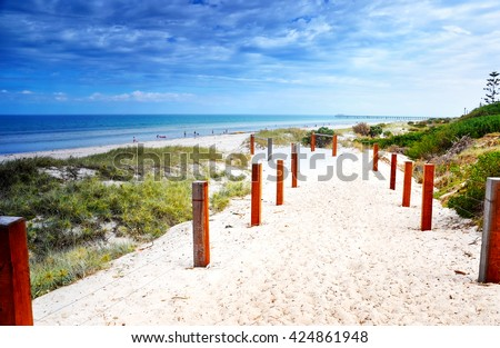 Path leading down to the beach with jetty in background, and clean blue ocean. - stock photo