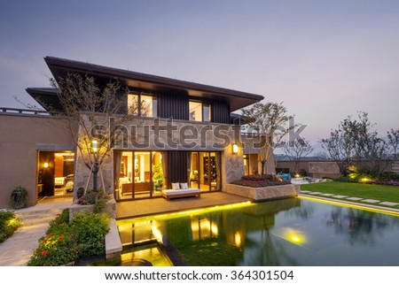path near pond to modern building at twilight - stock photo