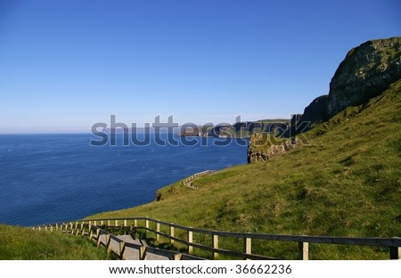 Path on coastline of Northern Ireland with sea and cliffs - stock photo