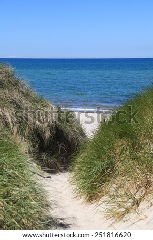 Path through sand dunes leading to the beach - stock photo