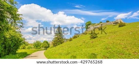 Path through valley Eselsburger Tal near river Brenz - jewel of the swabian alps (Schwaebische Alb), meadow hill with rocks on the right - stock photo
