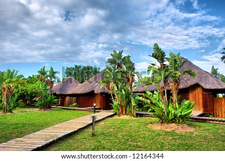 Path to wooden African chalets. Shot near Sodwana Bay nature reserve, KwaZulu-Natal province, Southern Mozambique area, South Africa. - stock photo