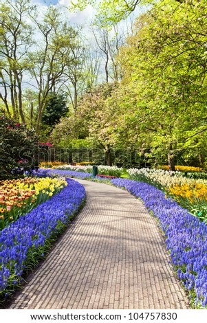Path with spring flowers in Keukenhof - stock photo