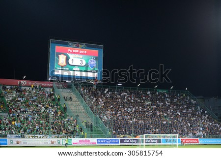 PATHUMTHANI, THAILAND- AUG12: Football fans on the stand cheer in action during Thai Premier League 2015 between BGFC and BuriramUtd at Leo Stadium on August 12, 2015 in Thailand. - stock photo