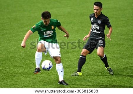 PATHUMTHANI, THAILAND- AUG12: Jetsadakorn Hemdaeng(L) of BGFC in action during Thai Premier League 2015 between BGFC and BuriramUtd at Leo Stadium on August 12, 2015 in Thailand. - stock photo