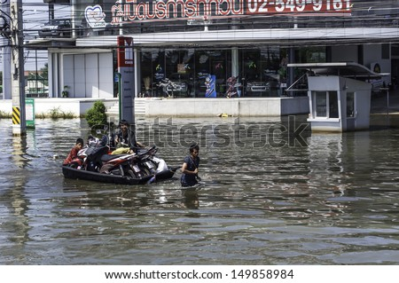 PATHUMTHANI, THAILAND - OCTOBER 30:People travel by boat due to the worst flood in Thailand for more than 50 years on October 30, 2011 in Pathumthani, Thailand.