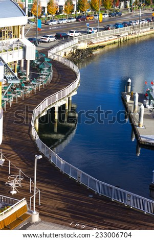 Pathway along the pier in Seattle downtown. Scenic view on the waters of Puget Sound in late afternoon in autumn. - stock photo