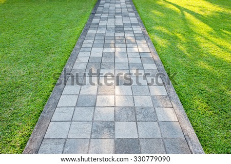 Pathway and green lawn in the park. - stock photo