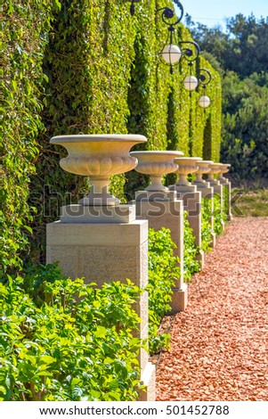 pathway in a garden park with line of stone vases