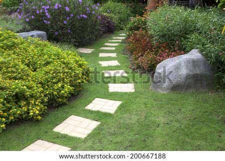Pathway in a Peaceful Green Park with flowers. - stock photo