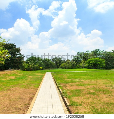 Pathway in beautiful park over blue sky
