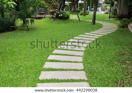 pathway in the park,curve walkway with stone tile on green grass field and flower garden.yard with table and chair set.