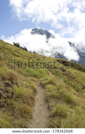 Pathway of trekking at Mount Rinjani with blur grass and tree (windy) and mount cover by cloud - stock photo