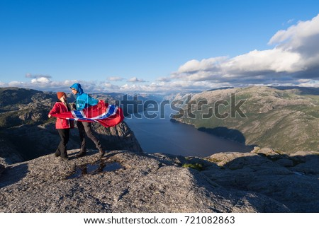 Pathway Preikestolen, Norway. Loving couple with the flag of Norway. Panorama of Lysefjord