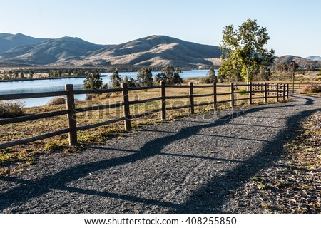 Pathway, trees, lake and mountains at Mountain Hawk Park in Chula Vista, California.  - stock photo