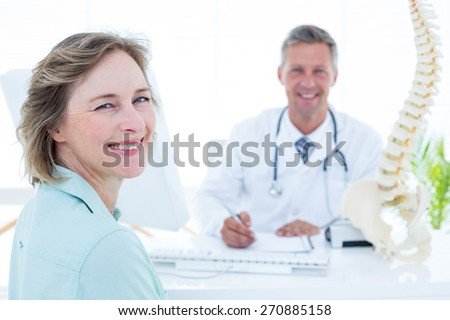 Patient and doctor smiling at camera in medical office - stock photo