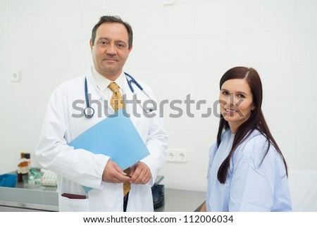 Patient and doctor together in an examination - stock photo