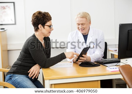 Patient And Male Doctor Communicating Over Digital Tablet - stock photo