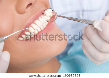 Patient at dentist office. Close-up of young woman sitting at the chair in dental office and smiling while doctor examining her teeth - stock photo
