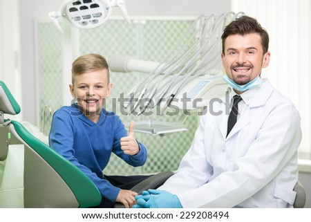 Patient at dentist office. Dentist and little patient are looking at camera and smiling. - stock photo