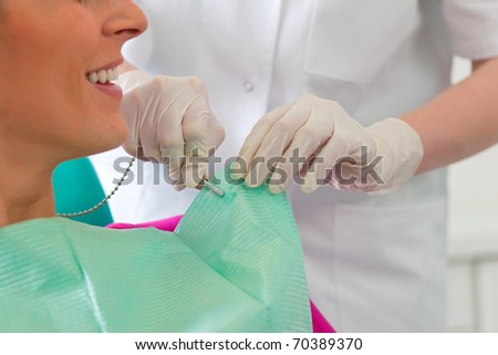 Patient at the beginning of a treatment � Assistant is putting the protection on