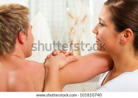Patient at the physiotherapy doing physical exercises with his therapist - stock photo