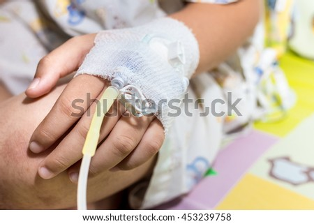 Patient child hand with saline intravenous (iv) in hospital