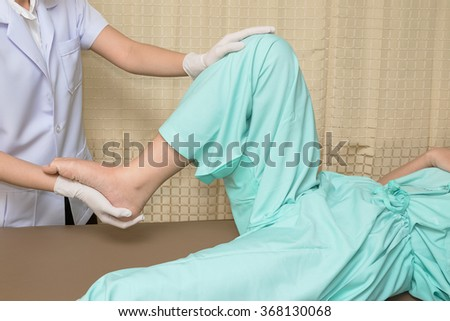 Patient doing knee exercises with physical therapist , in rehabilitation clinic - stock photo