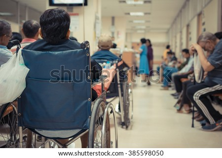 Patient elderly on wheelchair and many patient waiting a doctor and nurse in hospital , process in vintage style - stock photo