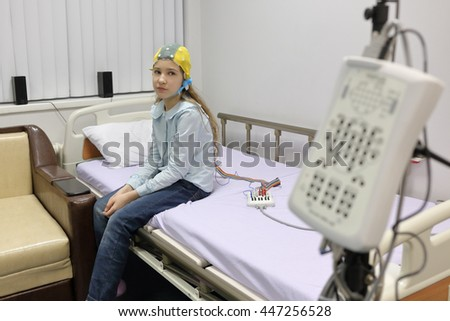 patient girl on procedure of recording of electroencephalogram, sitting on bed looking at camera - stock photo