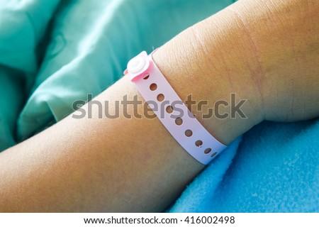 patient hand with hospital wrist tag,patient wristband name tag - stock photo