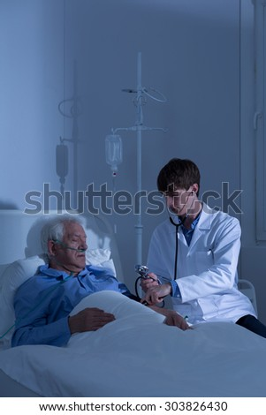 Patient having measured blood pressure in hospice - stock photo