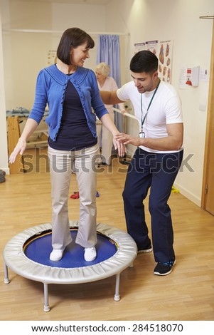 Patient Having Physiotherapy On Exercise Bike In Hospital - stock photo