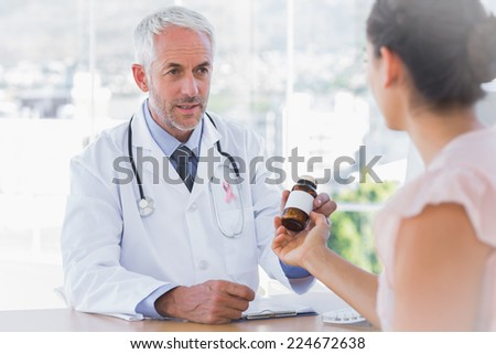 Patient holding jar of medicine wearing breast cancer awareness ribbon - stock photo